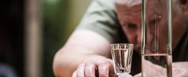 Mann mit Alkoholproblem sitzend vor Flasche mit Schnaps