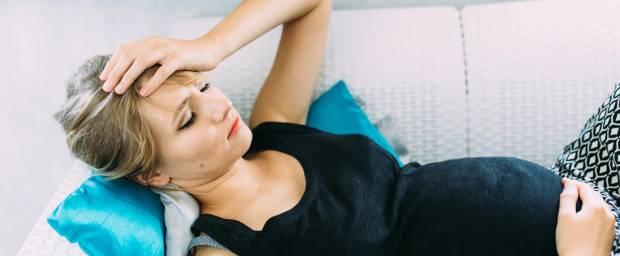 Müde, schwangere Frau auf dem Sofa liegend