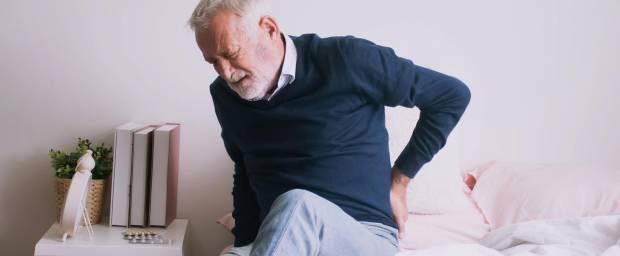 Älterer Mann mit Schmerzen beim Aufstehen aus dem Bett
