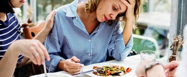 Frau mit Appetitlosigkeit sitzt vor einem Teller mit Essen
