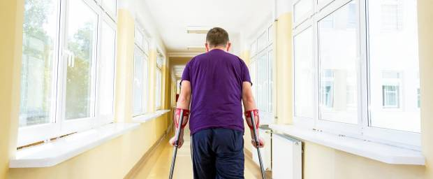 Mann auf Krücken nach arthroskopischer Behandlung am Knie