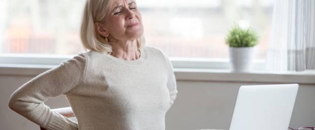 Ältere Frau mit Rückenschmerzen vor Laptop sitzend