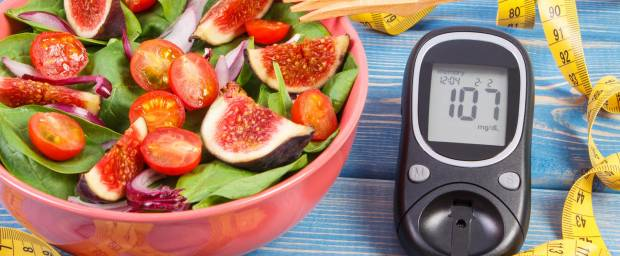 Frischer Salat mit Ost und Gemüse in Schüssel mit Maßband und Blutzuckermessgerät auf einem Tisch