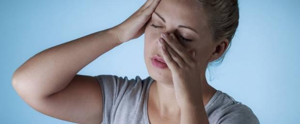 Frau hält sich die Nase - Schmerzen in den Nasennebenhöhlen