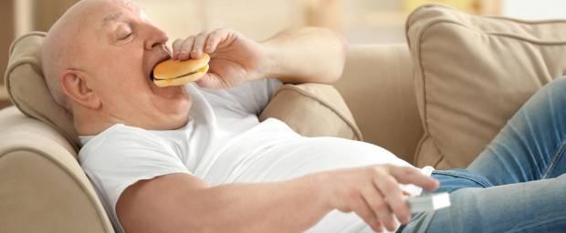 Senior auf der Couch mit Burger und Fernbedienung in der Hand