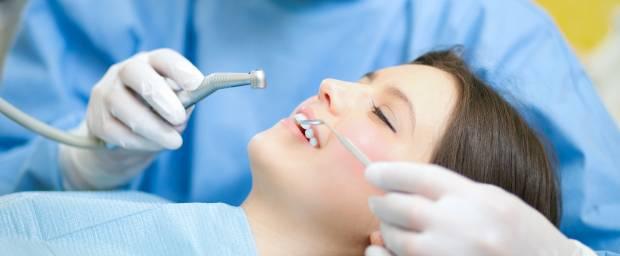 Frau während Zahnbehandlung beim Zahnarzt