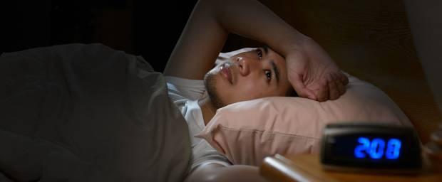Junger Mann mit Durchschlafstörungen in der Nacht