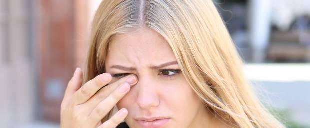 Frau reibt sich das Auge