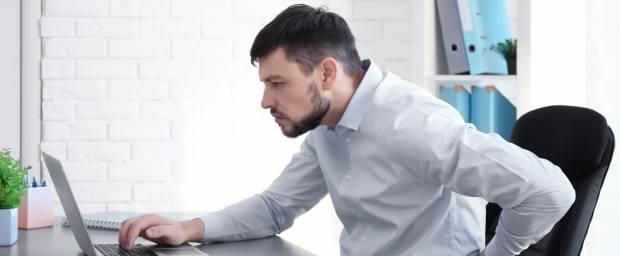 Mann mit Fehlhaltung und Rückenschmerzen vor dem Computer