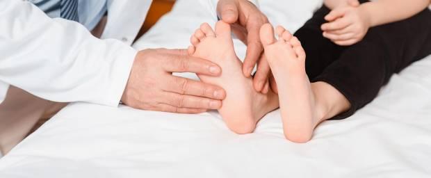 Arzt untersucht Füße eines Kindes