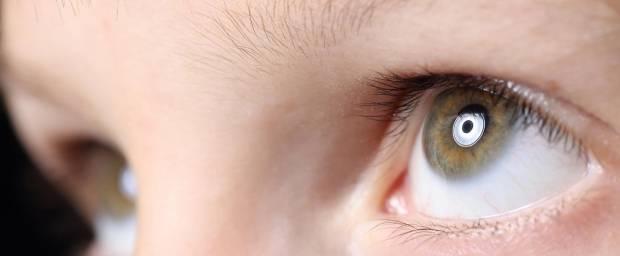 Kind schaut in ein Licht, dass sich in seinen Augen reflektiert