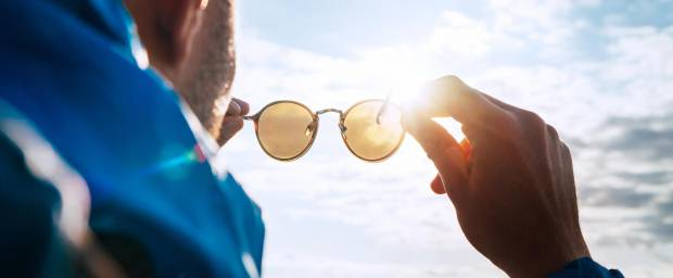 Mann hält Sonnenbrille schützend vor die Sonne