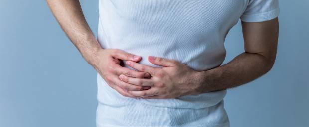 Mann hält sich die Hände am Bauch vor Schmerzen