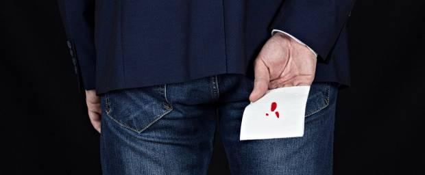 Mann in Rückenansicht hält blutiges Toilettenpapier