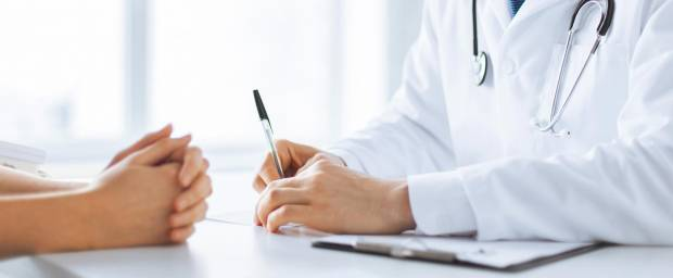 Arztgespräch mit Nahaufnahme der Hände von Arzt und Patientin