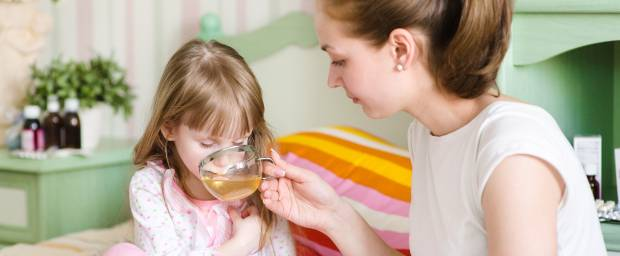 Mutter gibt krankem Kind etwas zu trinken