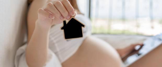 Schwangere mit einem Häuschen-Modell in der Hand