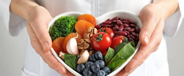 Ärztin hält Schüssel in Herzform mit frischem Obst, Gemüse, Trockenobst