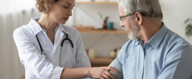 Ärztin misst Blutdruck bei älterem Patienten