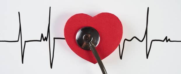Stethoskop mit rotem Herz auf Kardiogramm liegend