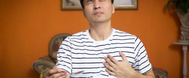 Asiatischer Mann mit Herzproblemen während dem Essen
