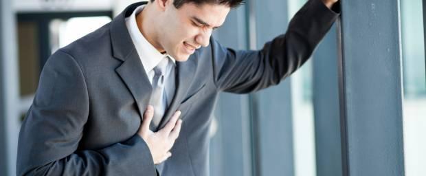 Junger Mann mit Herzschmerzen wegen Stress im Büro