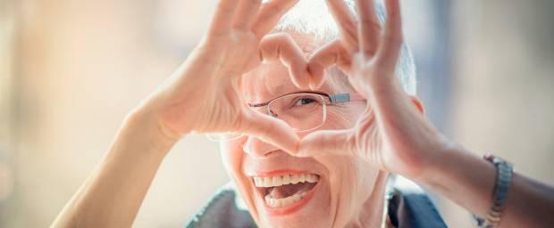 Seniorin formt Herz mit ihren Fingern