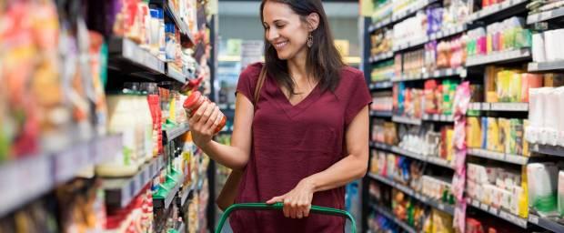 Frau zwischen Supermarktregalen mit Glas in der Hand