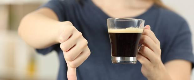 Frau mit Kaffeetasse in der Hand und die anderen Hand zeigt mit dem Daumen nach unten