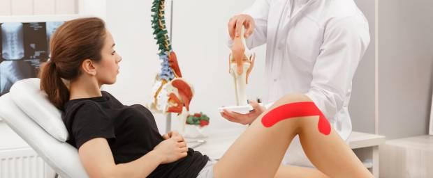 Arzt erklärt etwas Patientin mit einem Tape am Knie