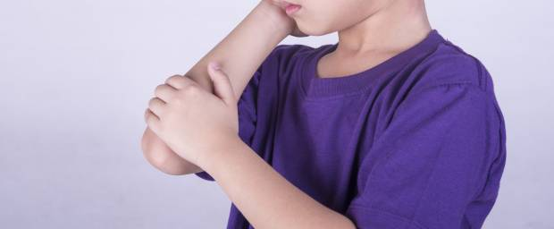 Asiatischer Junge mit Gelenkschmerzen im Arm