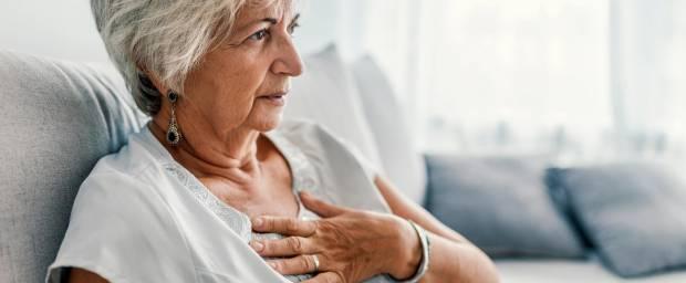 Ältere Frau mit Atembeschwerden sitzend auf dem Sofa