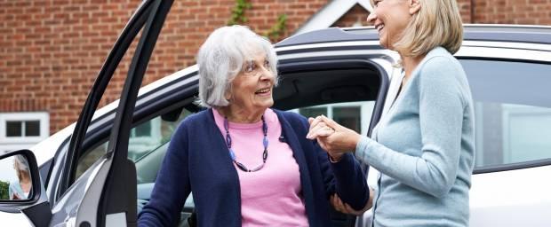 Ältere Frau wird beim Aussteigen aus dem Auto geholfen