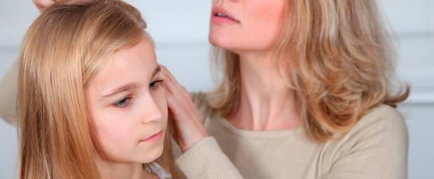 Mutter schaut sich die Haare und die Kopfhaut ihrer Tochter an