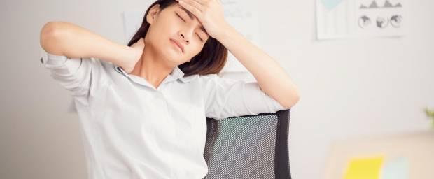 Frau im Büro mit Kopf- und Nackenschmerzen