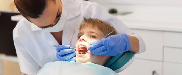 Zahnärztin bei Zahn-Behandlung eines Jungen