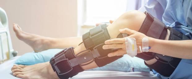 Frau mit Knieschiene im Krankenbett