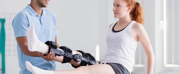 Frau mit Orthese am Bein bei Krankengymnastik