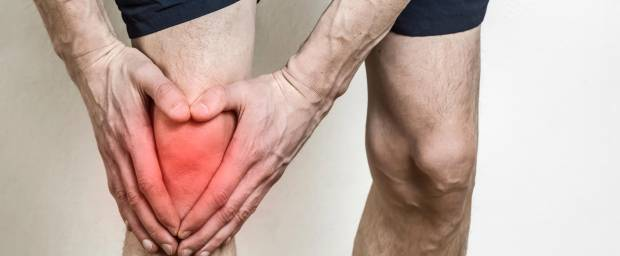 Mann hält sich das rot eingefärbte Knie wegen Schmerzen
