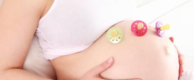 Schwangere Frau mit drei Schnullern auf ihrem Bauch