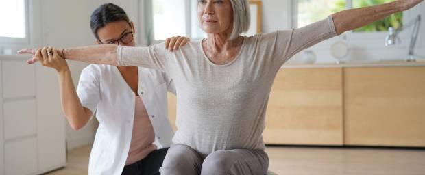 Seniorin bei Übung auf dem Gymnastikball unter Anleitung einer Therapeutin