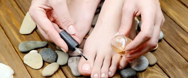 Frau behandelt Ihre Fußnägel mit spezieller Tinktur