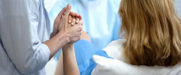 Frau bei einer Spontangeburt drückt die Hand ihres Mannes