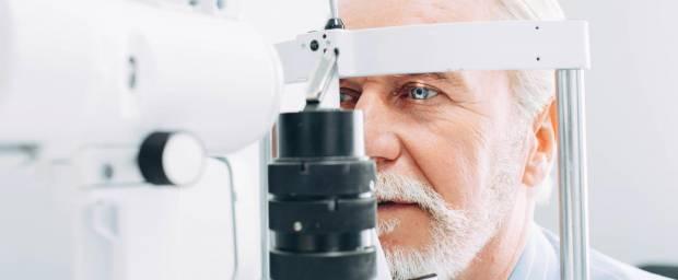 Älterer Mann bei Augenuntersuchung an Messgeraet