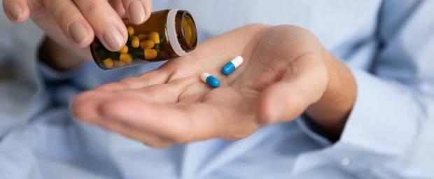 Frau nimmt sich zwei Pillen aus Pillengläschen auf die Hand