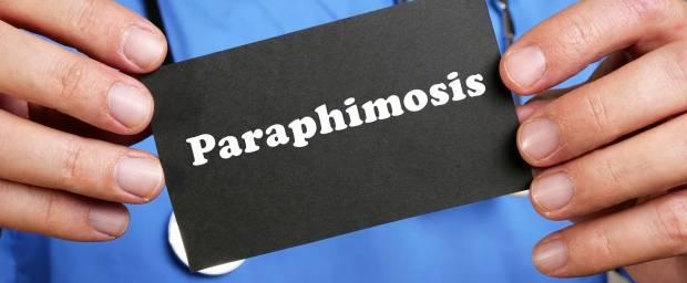 Arzt hält Schild mit Aufschrift Paraphimosis in der Hand