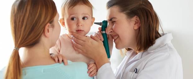HNO-Arzt schaut Kleinkind ins Ohr