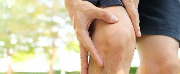 Mann hält sich das Knie