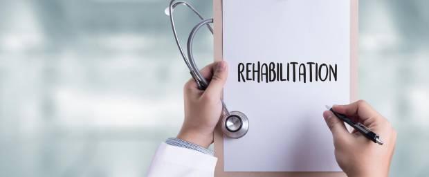 Das Wort Rehabilitation von einem Arzt auf einem Papier geschrieben, dass an einem Klemmbrett hängt