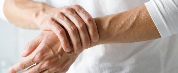 Mann fasst sich an das Handgelenk